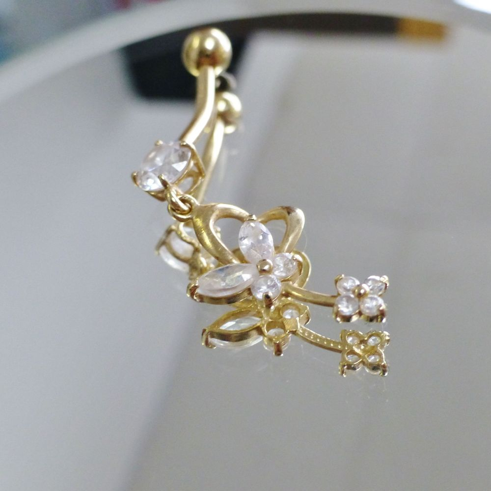 close up picture of a yellow gold round and marquise cut cubic zirconia dangle butterfly loop heart belly button ring