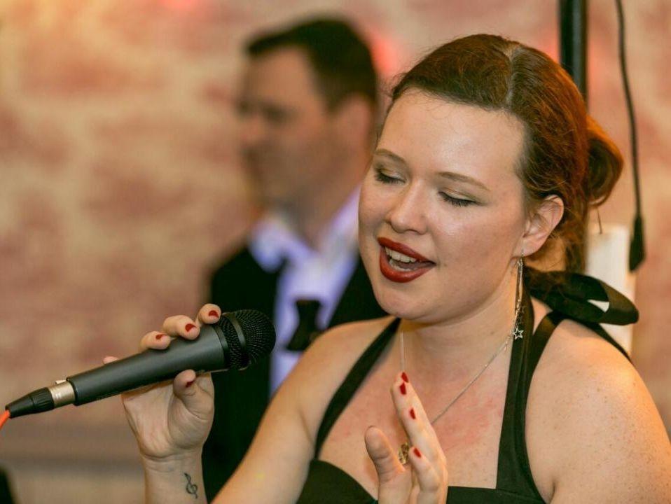 Anne Oosthuizen met microfoon demonstreert zang