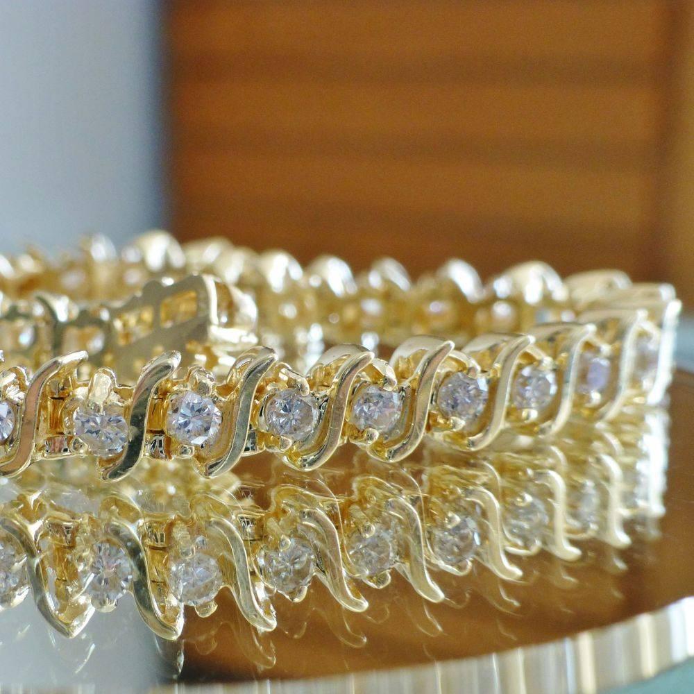 closeup picture of a yellow gold s link round cut diamond tennis bracelet