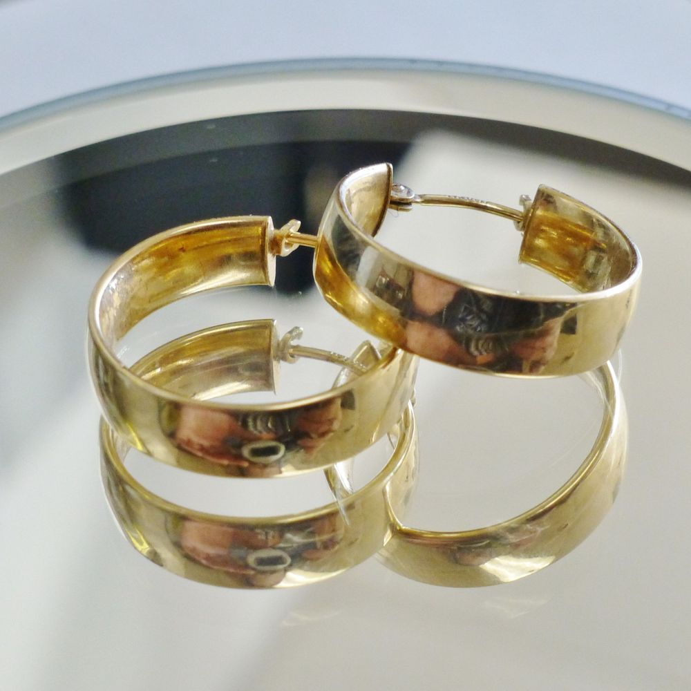 close up picture of a pair of yellow gold wide hoop earrings