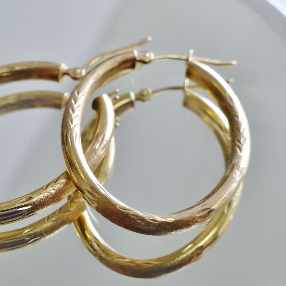 A pair of diamond cut yellow gold oval hollow hoop earrings