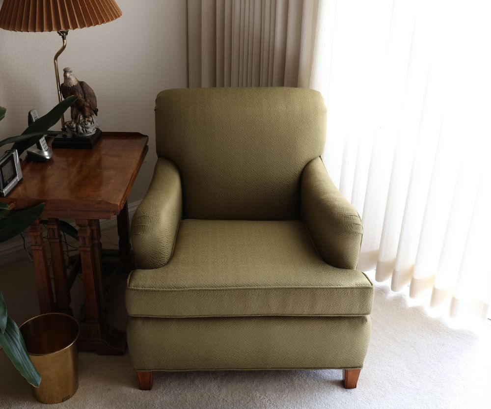 medium green chair shown in the interior of a room