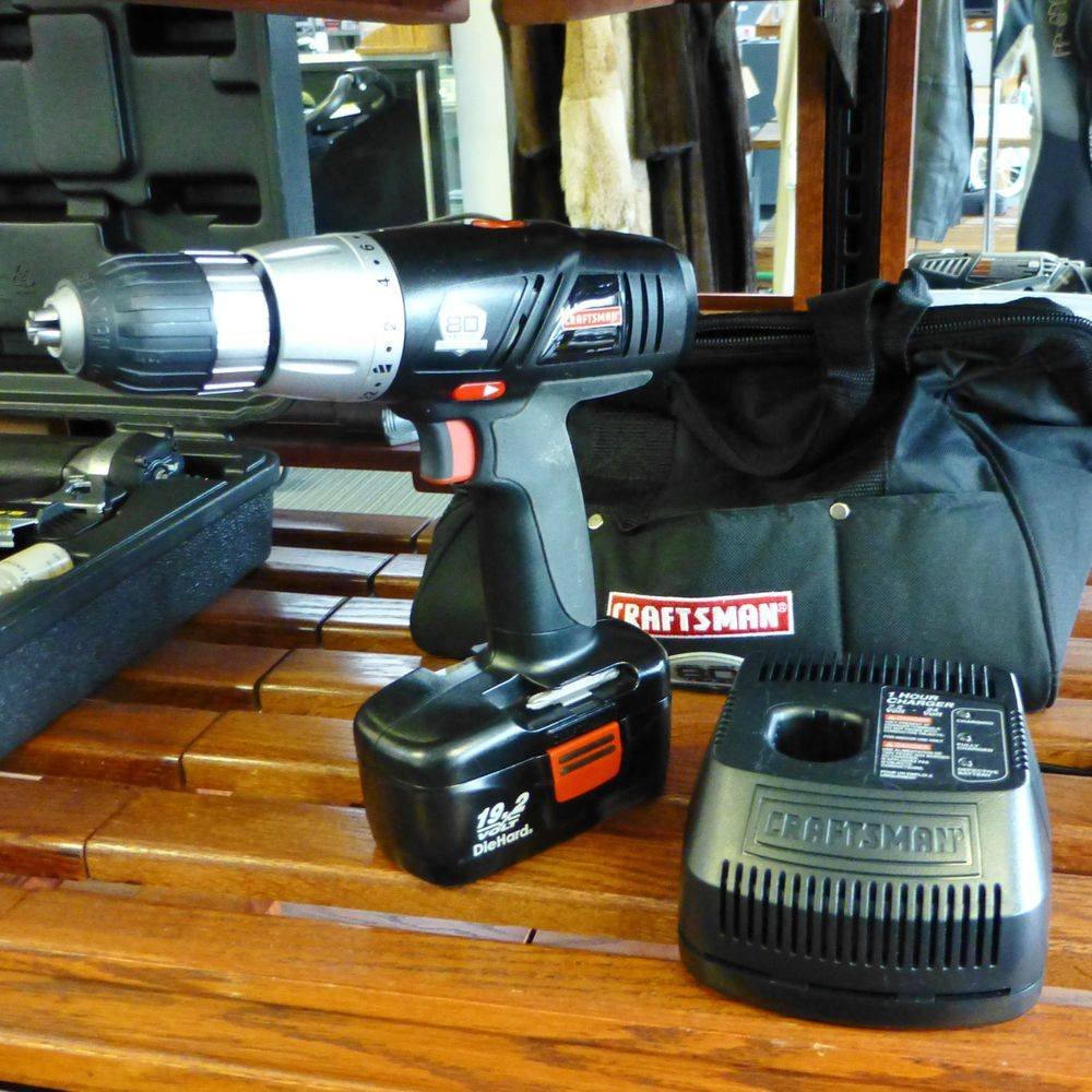black cordless drill with charger and battery on a shelf