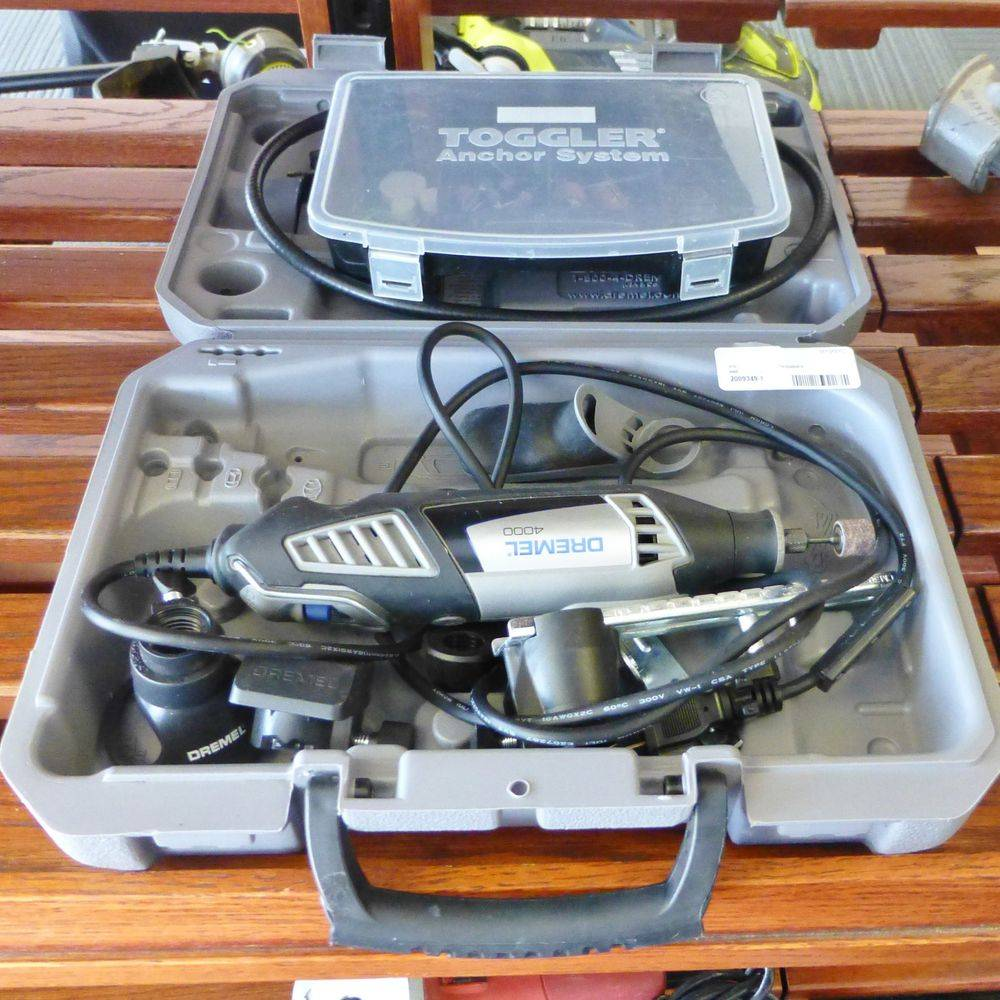 close up picture of a gray and black corded Dremel Tool Kit with accessories in a case