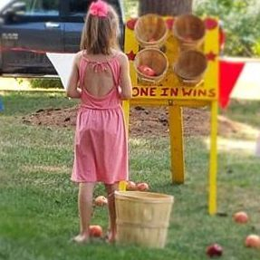Little girls playing a carnival apple toss game