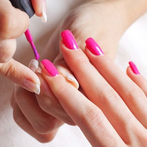 Manicurist painting nails on manicure course