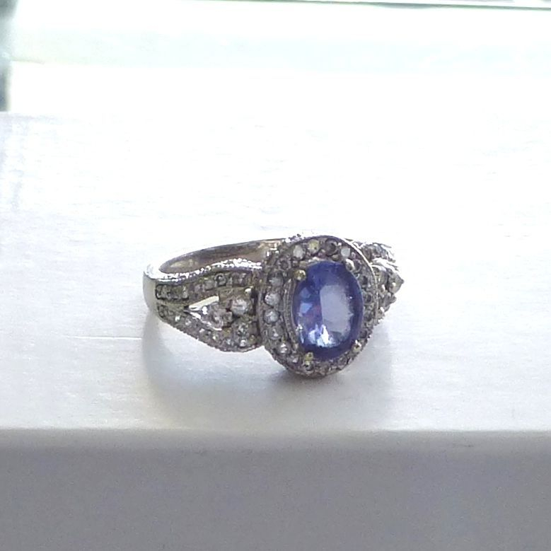 White Gold Gold Ring With A Purple Tanzanite Center Stone  Framed With A Diamond Halo With Side Accents And A Miligrain Design
