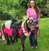 Girl standing next to a miniature horse dressed in a Hawaiian Lei