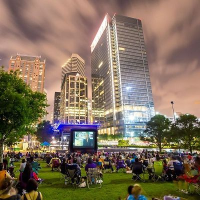 image of Houston's Discovery Green park at night,  people watching  movie on big screen