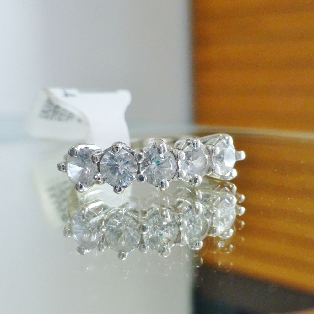 close up picture of a white gold ring with five round cut white sapphires