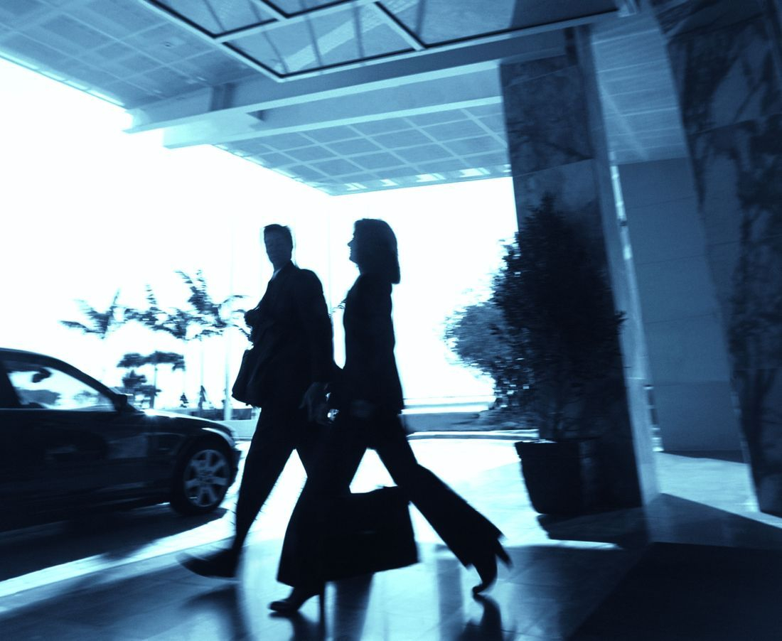 two business travellers walking towards a airport transfer car