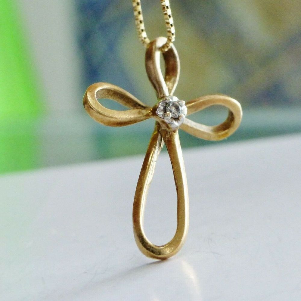 Yellow gold infinity cross with a center diamond accent charm