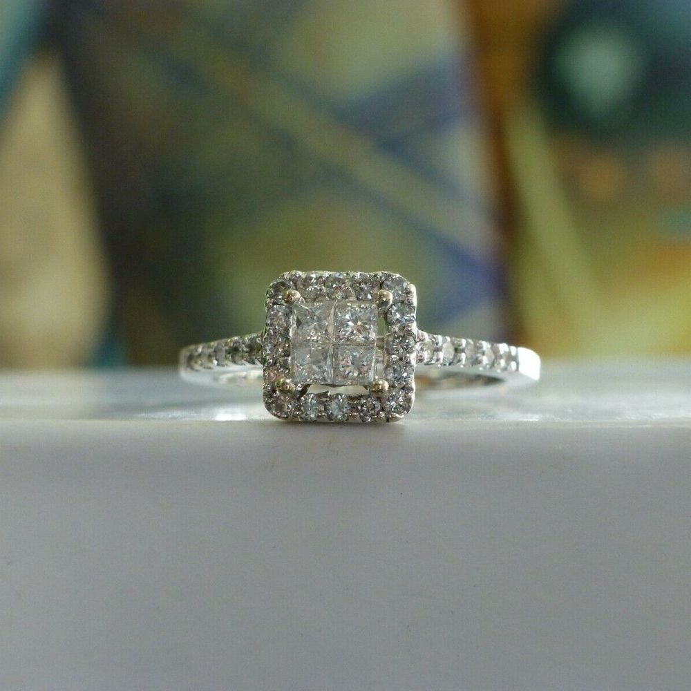 Four Princess Cut Diamond Cluster surrounded by round cut diamond square frame with round diamonds accenting the sides of a white gold engagement ring