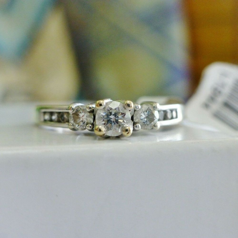 Three Round Cut Diamonds Prong Set and centered at the top of a white gold engagement ring, with side diamond accents