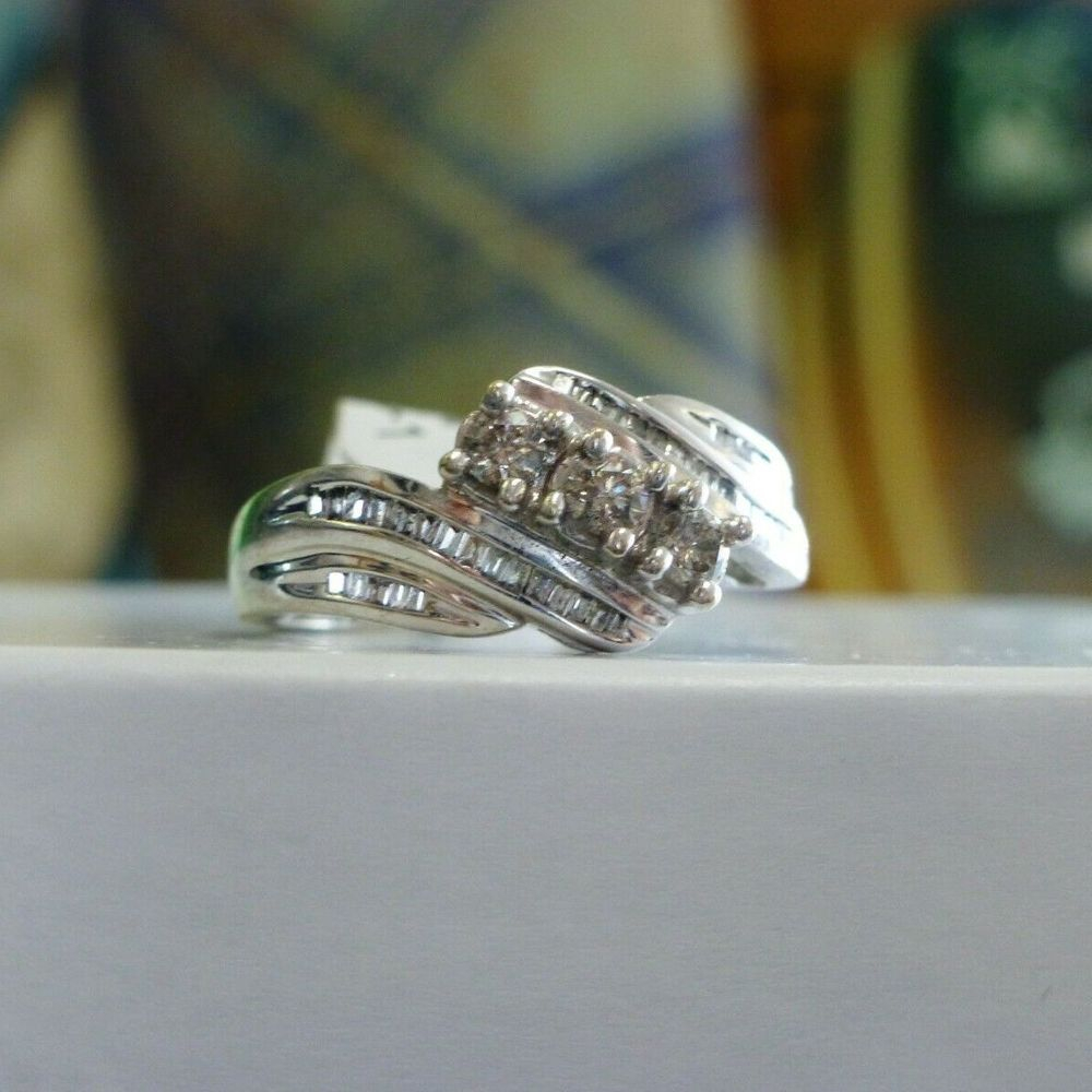 white gold round and baguette diamond cluster ring with a swirl design
