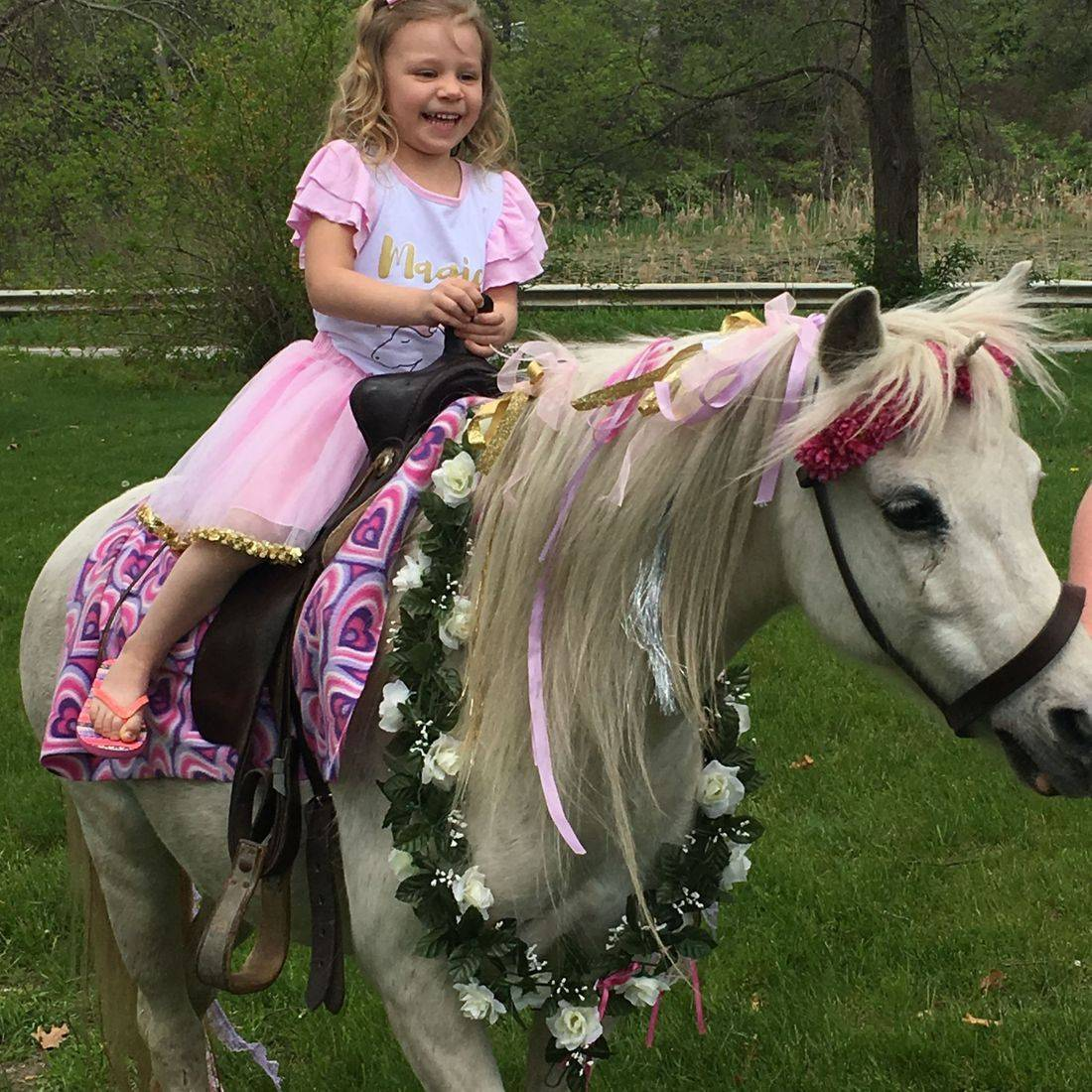 Little girl sitting on a unicorn with flowers around his neck