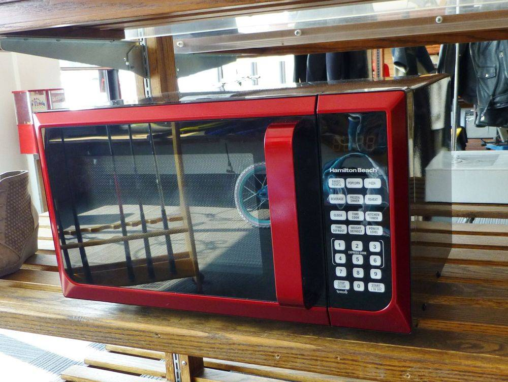 red microwave on a wooden shelf