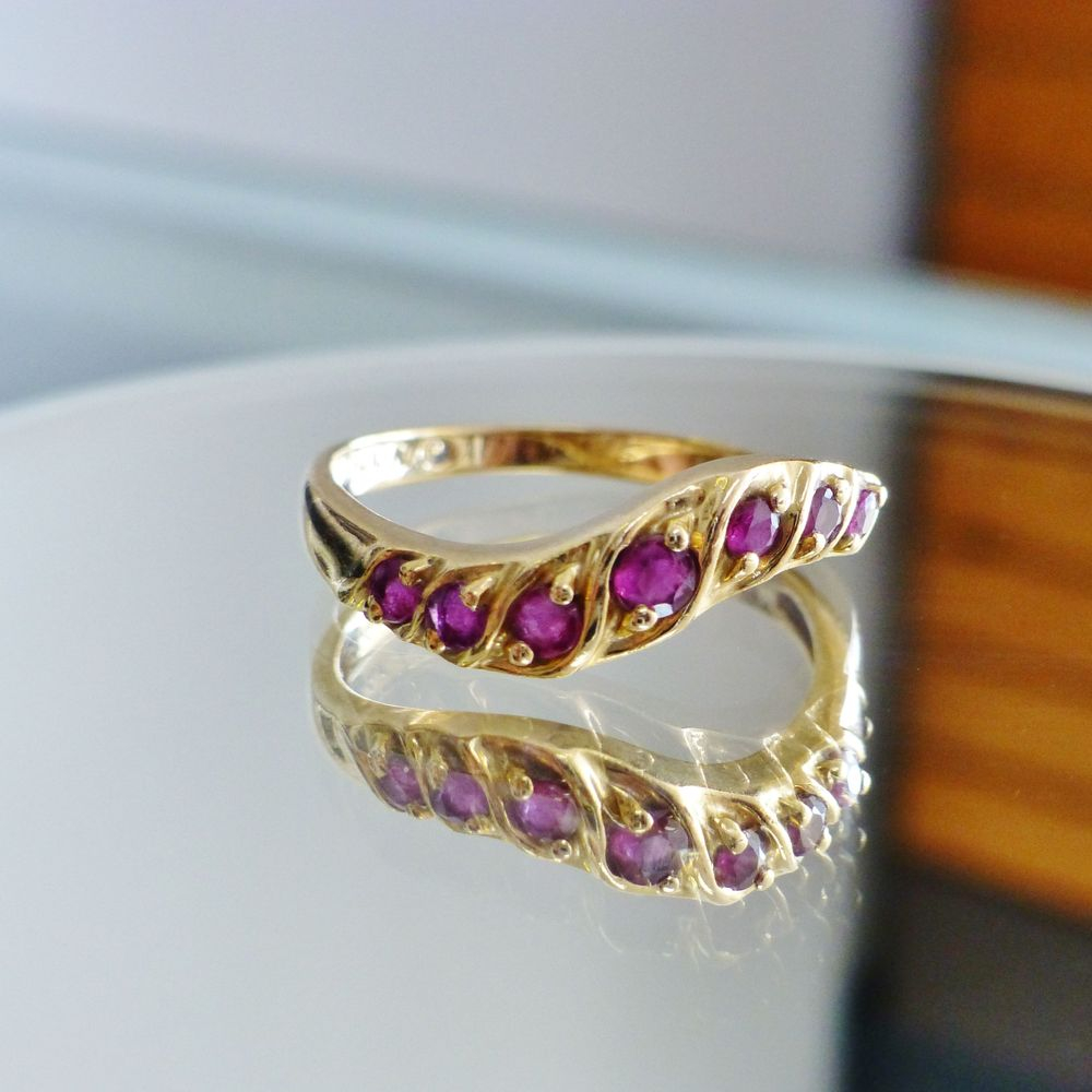 Closeup picture of a wavy design yellow gold ring with seven graduating rubys