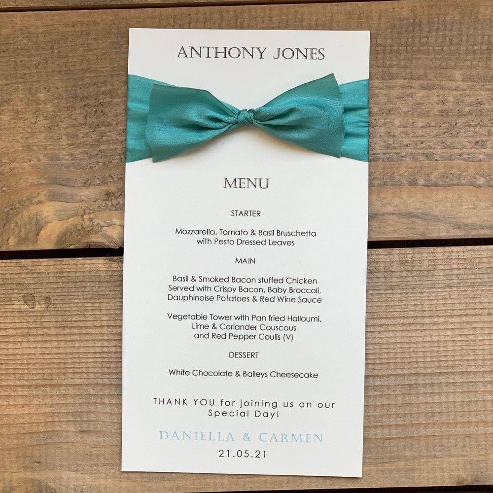 Ivory menu card printed with guest name  name and  teal pure silk ribbon bow