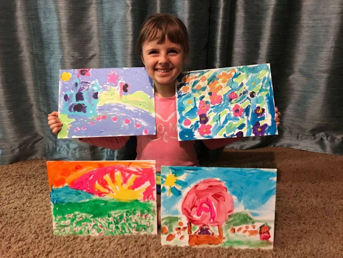 Young girl displaying four paintings she created using bright colors. One is a castle. One is a field of flowers. One is flowers and sunrise. One is a hot air balloon.