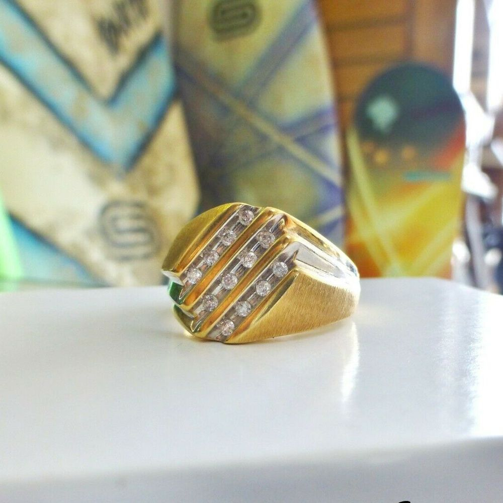 Three white gold rows set with round diamonds on top of a yellow gold ring with a satin finish