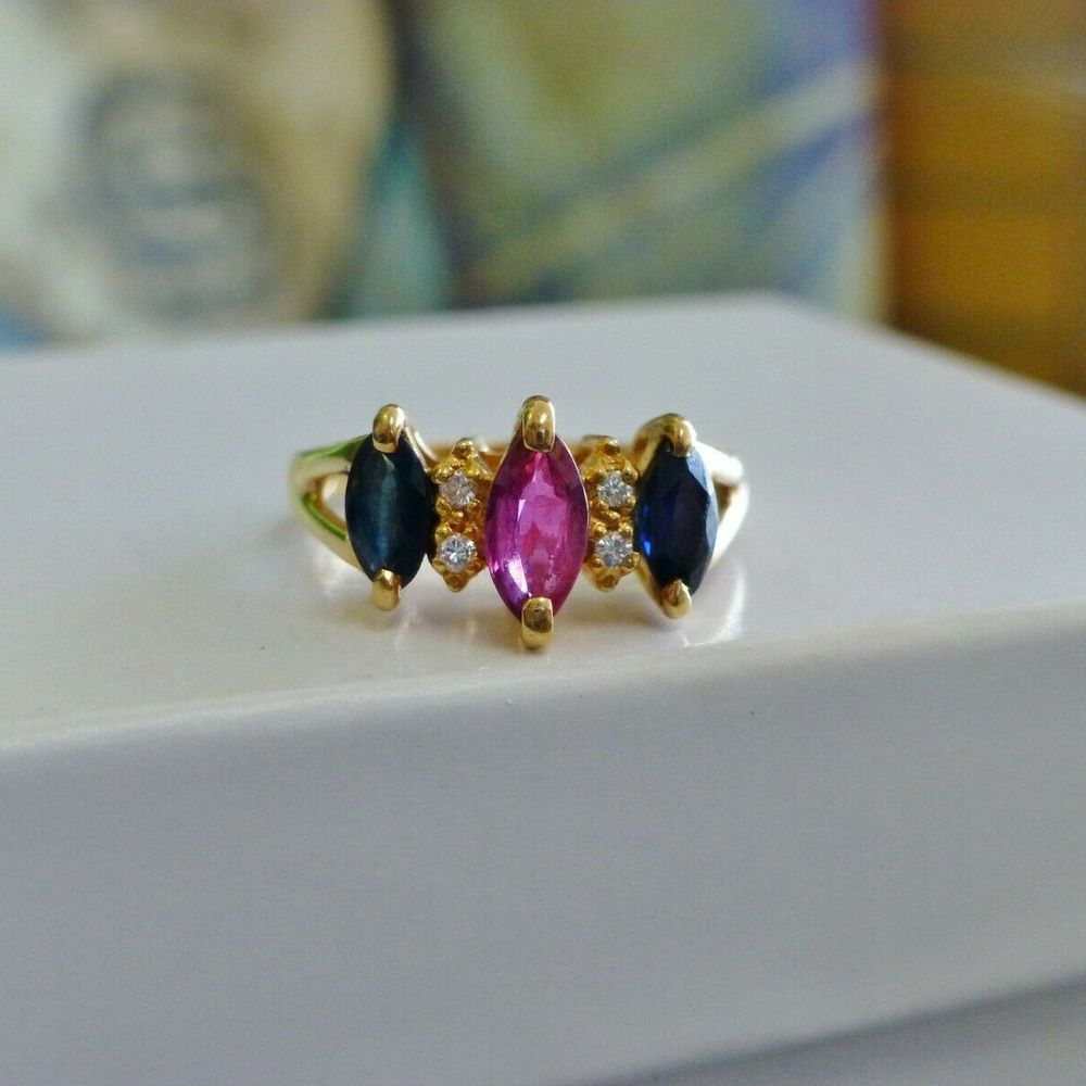 Marquise Ruby Prong set and centered between blue sapphire marquise and diamond accents in a yellow gold ring
