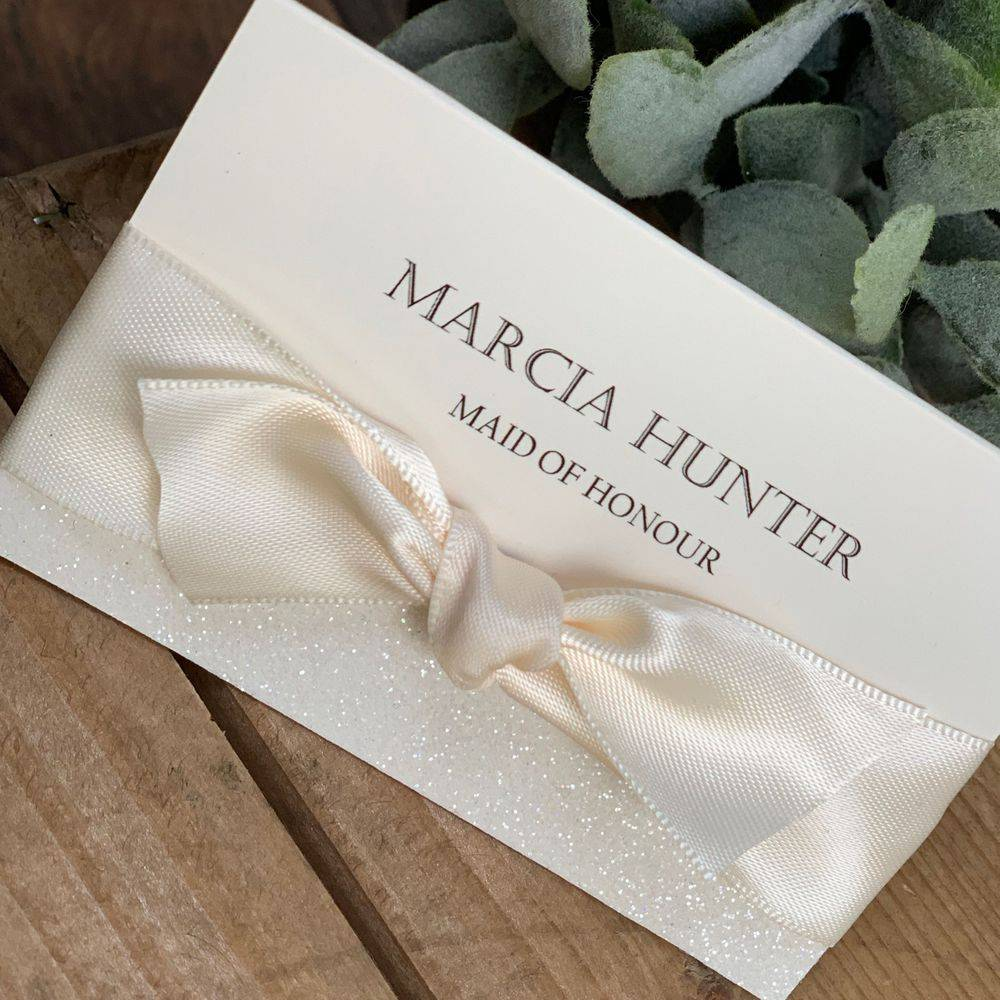 Ivory wedding place name card with ivory glitter and ribbon