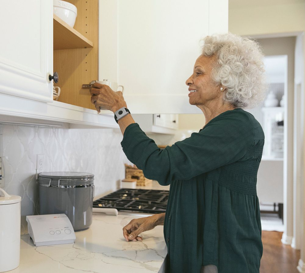 Independent women in her kitchen wearing the personal help button.