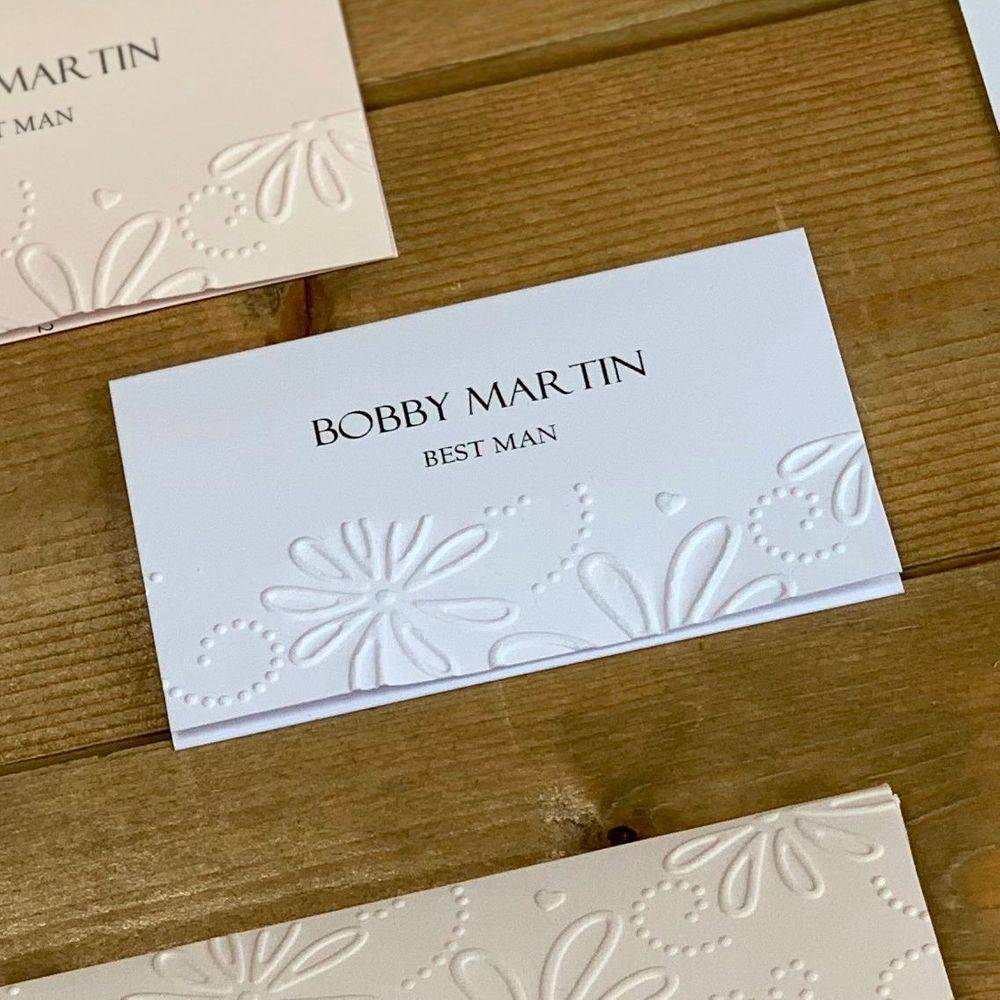 White embossed wedding place name card with daisy design