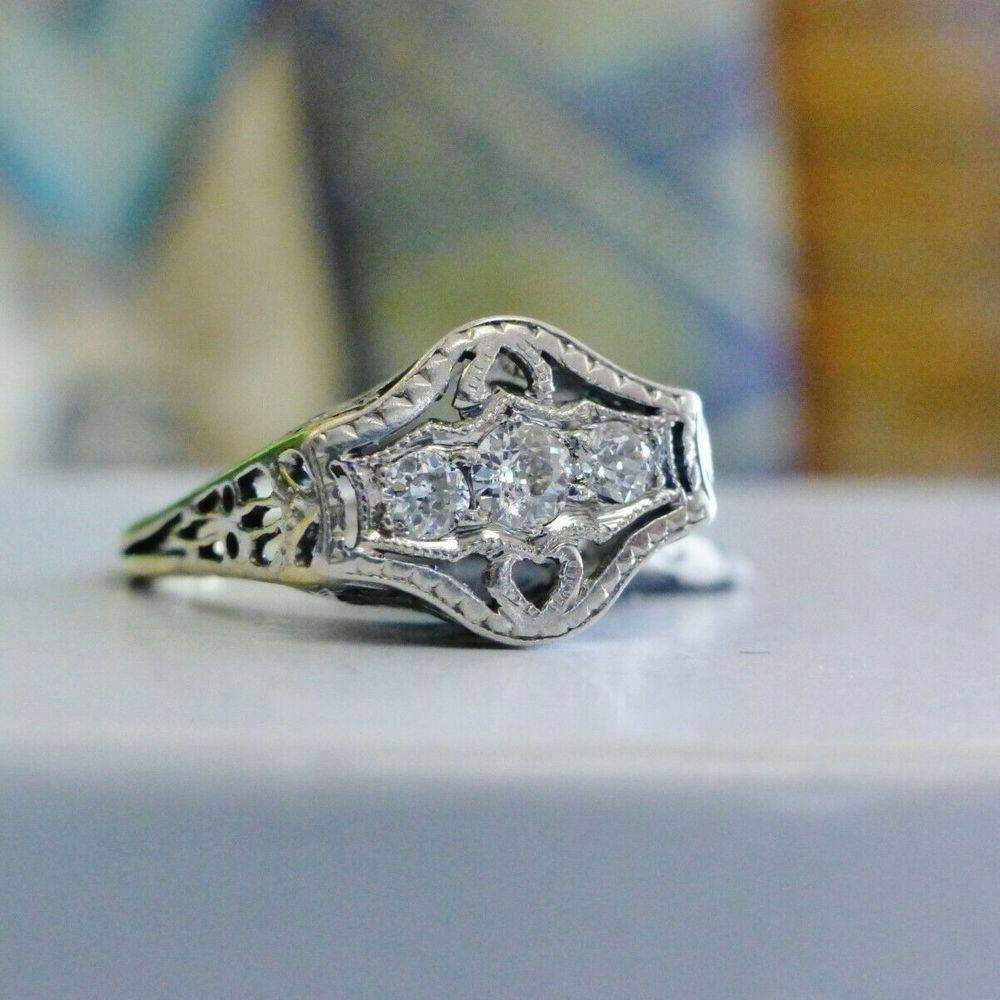 Three round diamonds prong set atop of an art deco style white gold ring