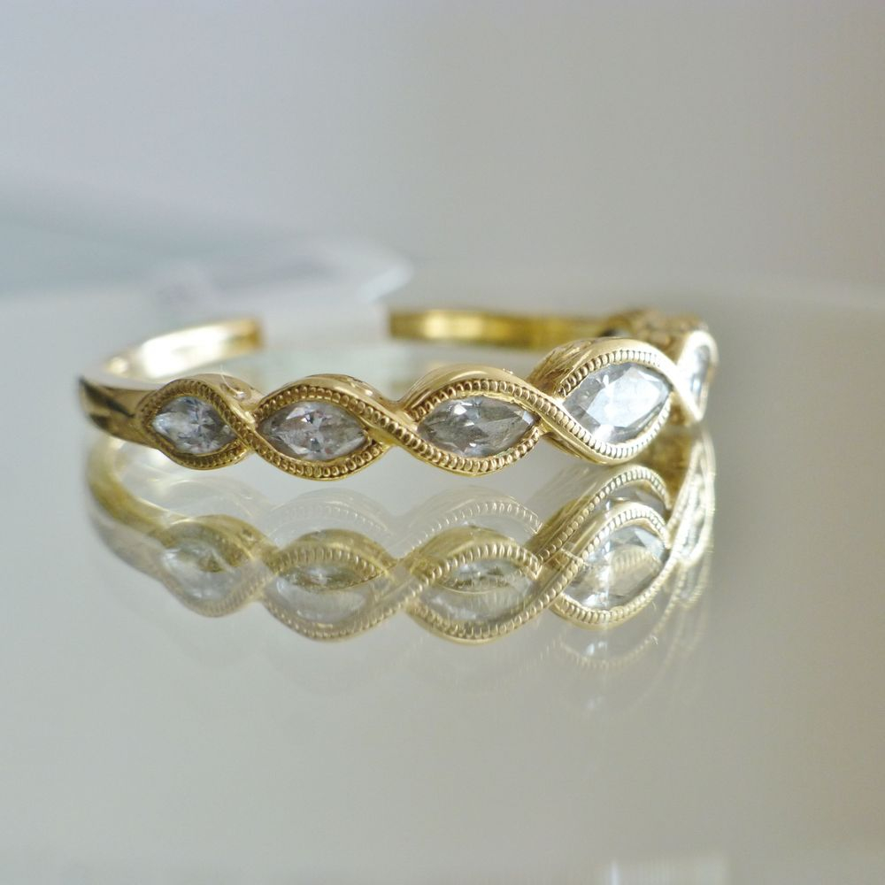 picture of a yellow gold twisted band with marquise daimonds