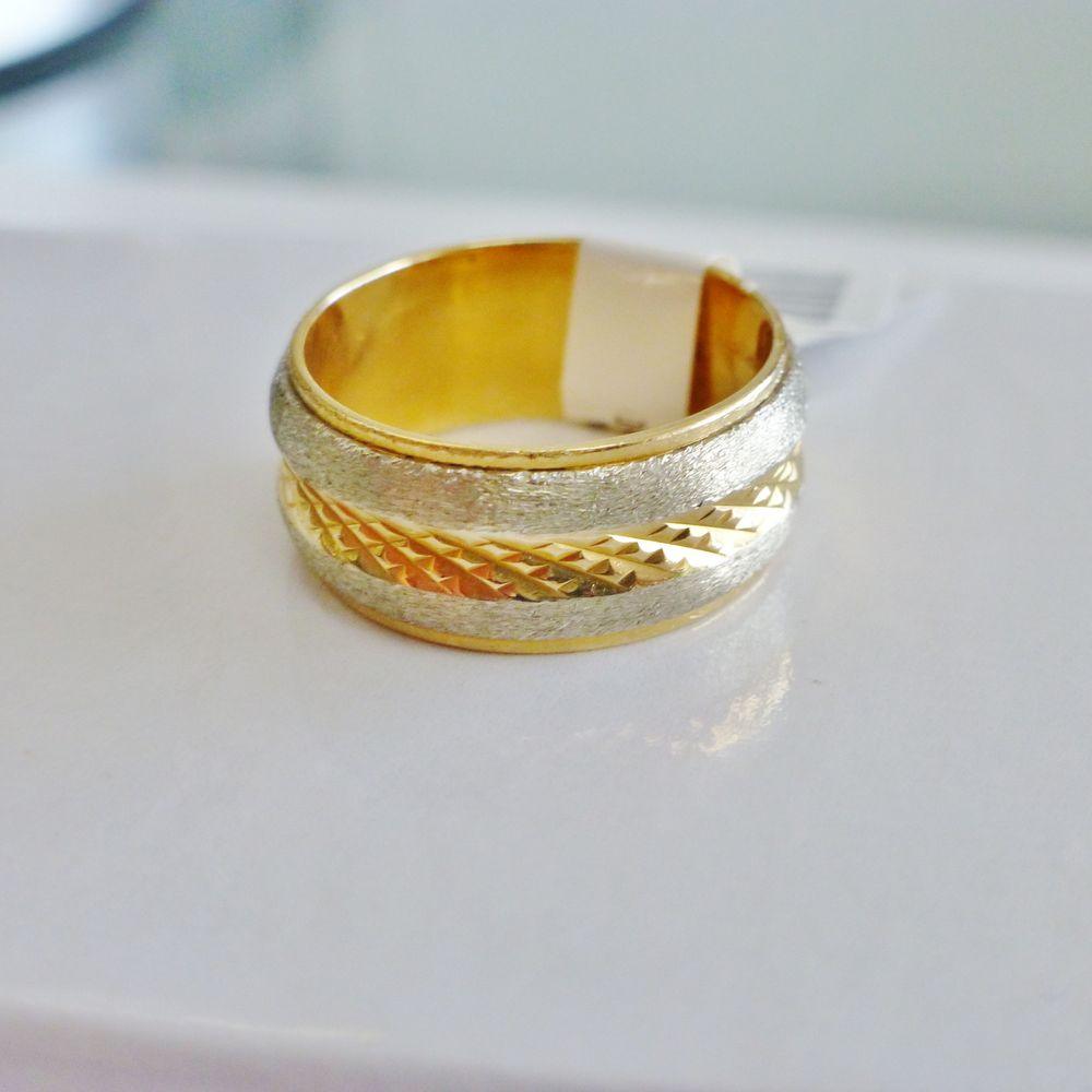 closeup picture of a two tone gold diamond cut wide band wedding ring