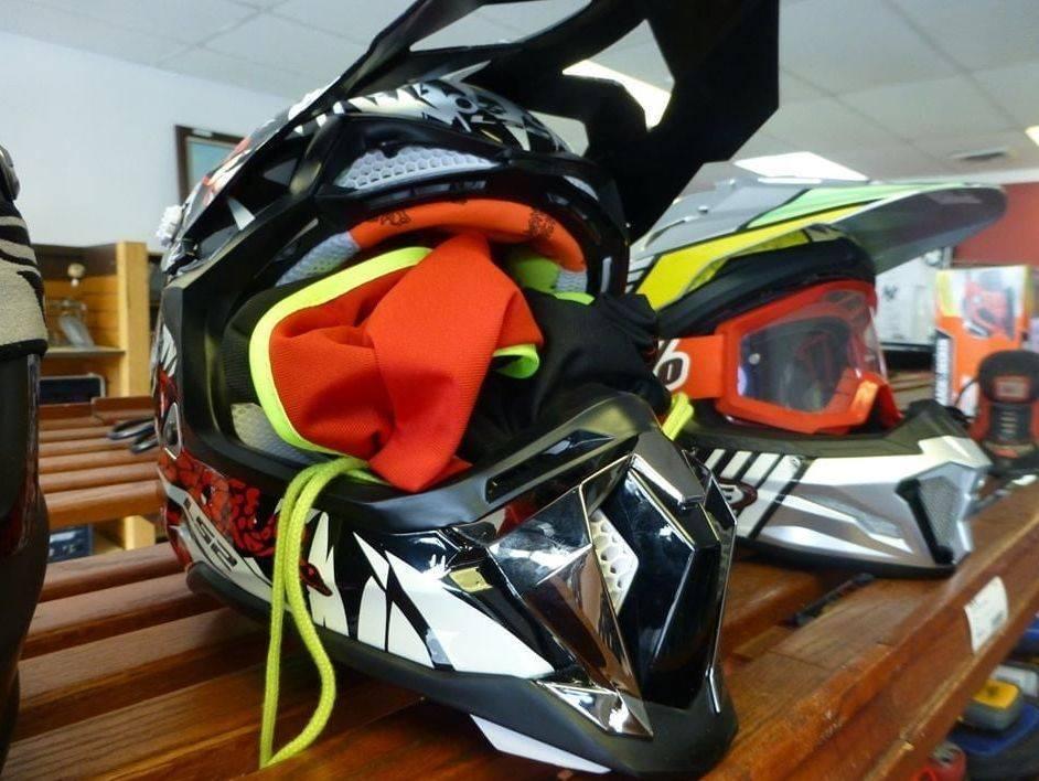 Black, red, white and yellow motocross helmet on wooden shelf