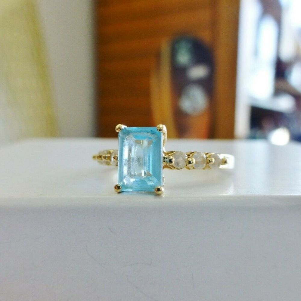Emerald Cut Sky Blue Topaz Prong Set Ring With Round White Sapphire Accents