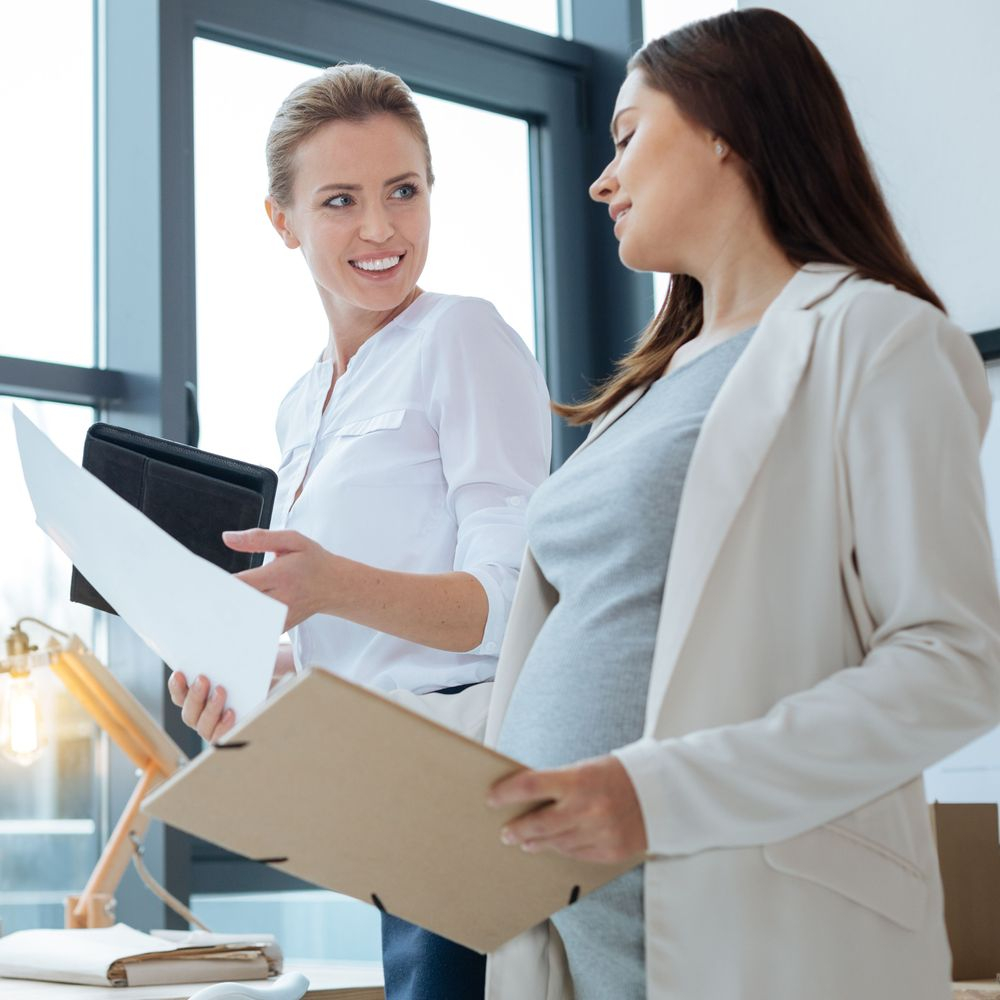 pregnant woman talking to colleague