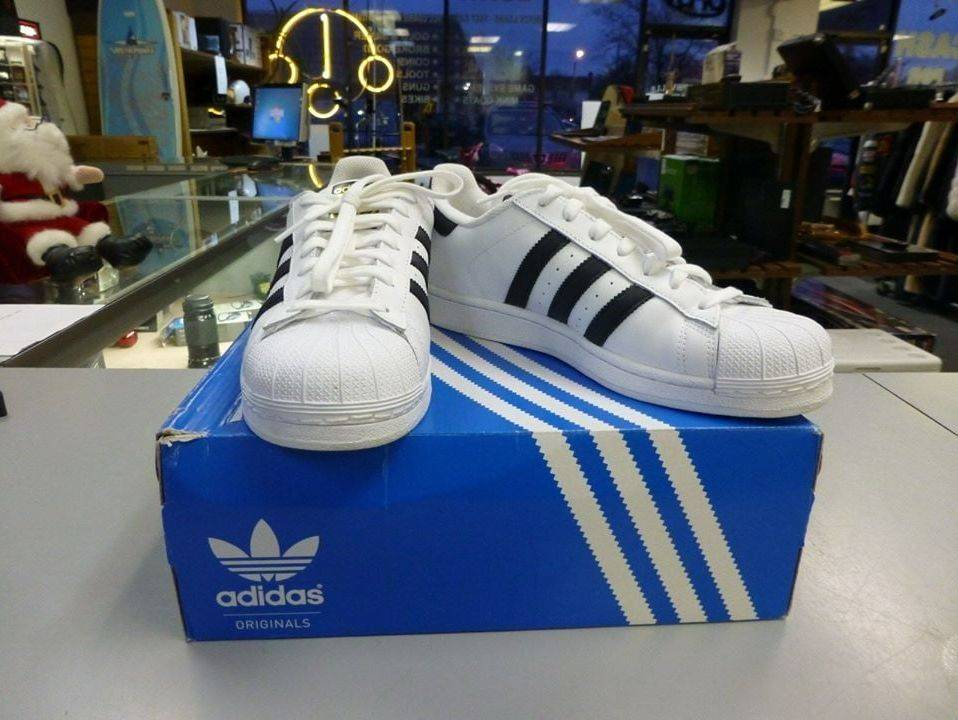 White Black and Gold Adidas Womens Shoes on a Blue Adidas Box