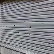 Vinyl siding hail damage caused holes in siding