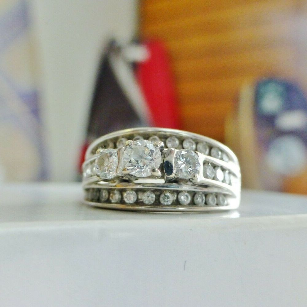 Round Cut Three Diamonds Centered in a white gold bridge style engagement Ring