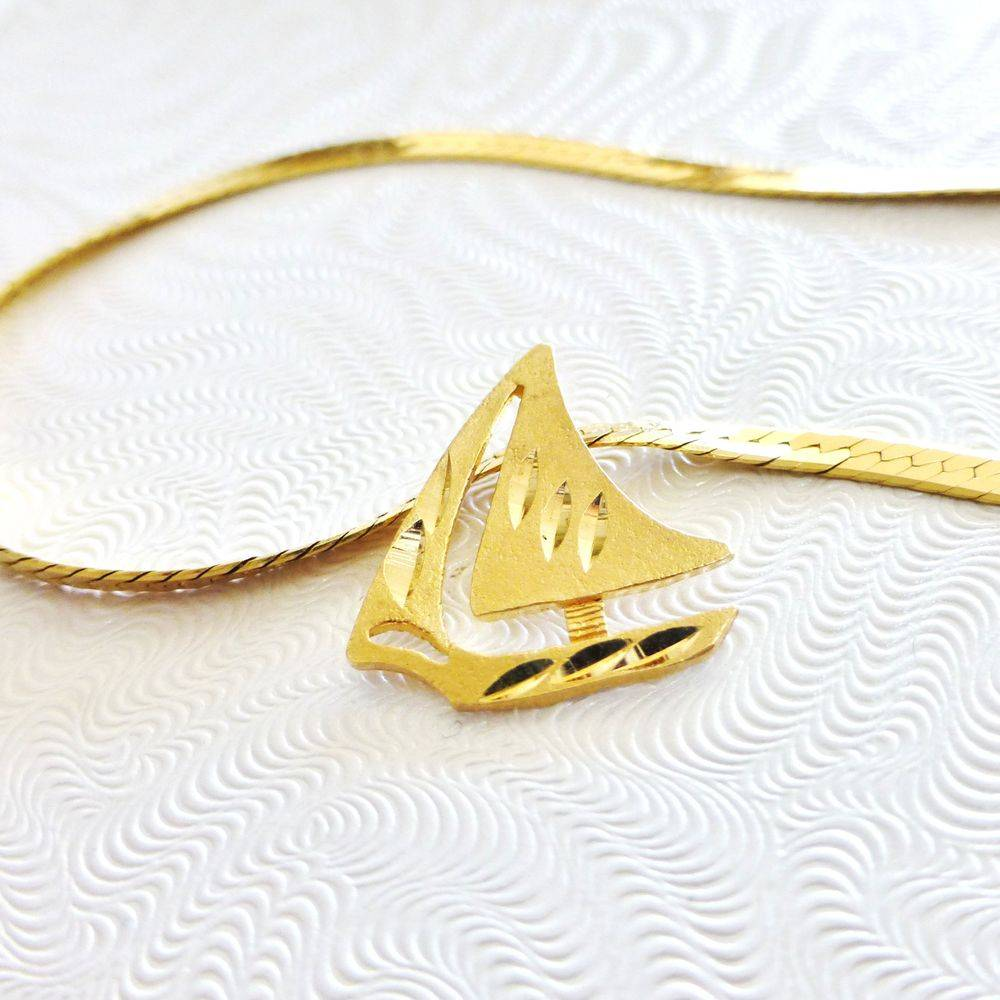 closeup picture of a yellow gold textured finish diamond-cut sailboat charm on a yellow gold herringbone necklace