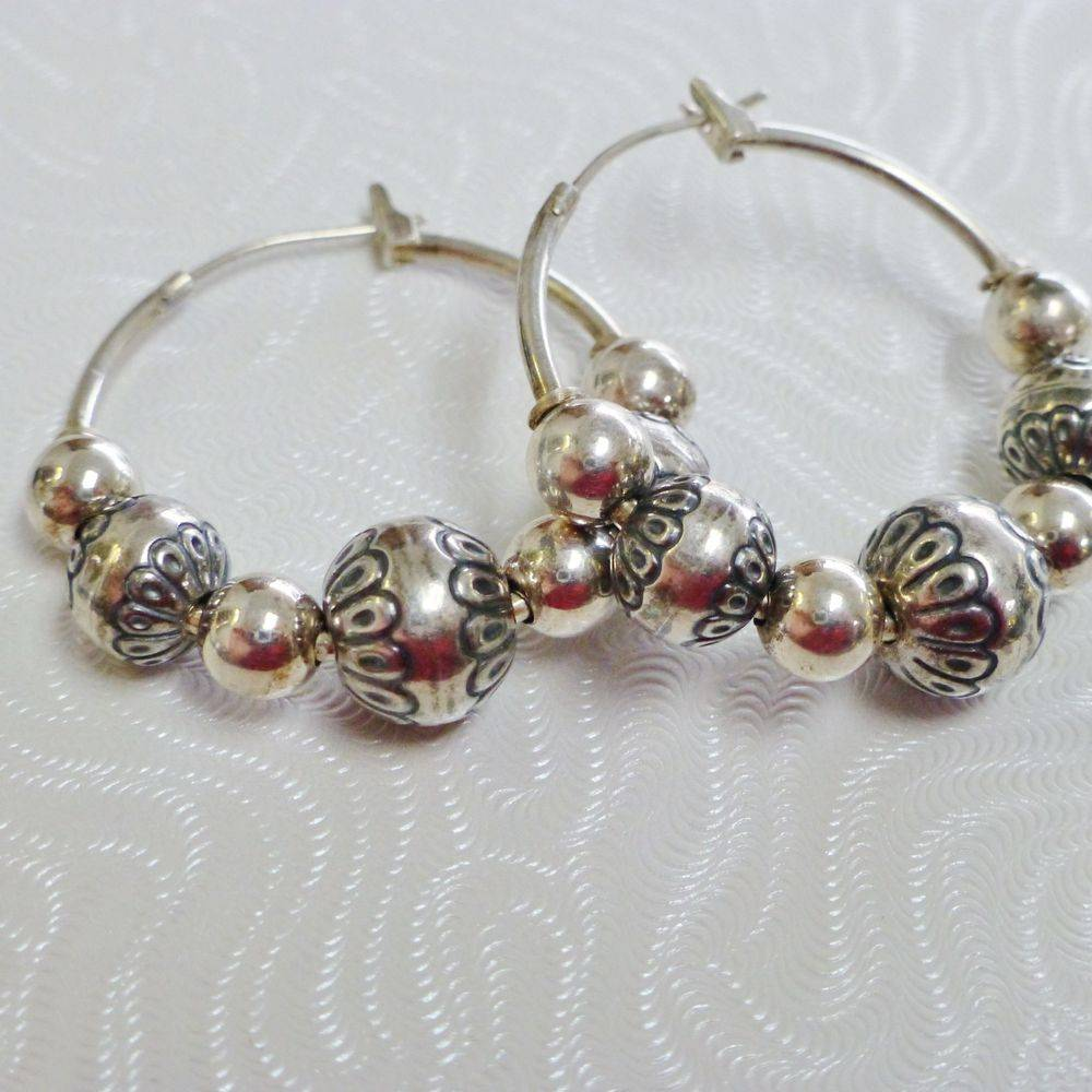 close up picture of a pair of sterling silver hoop earrings with textured beads