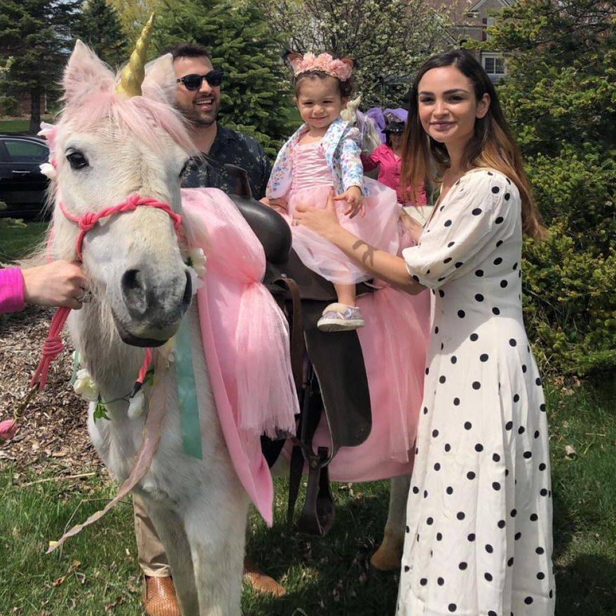 Girl wearing bunny ears standing next to white horse wearing bunny ears