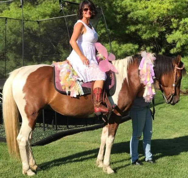 Woman in a white dress sitting on a paint horse