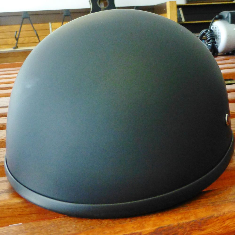close up picture of a matte black LDMET half shell helmet on a shelf