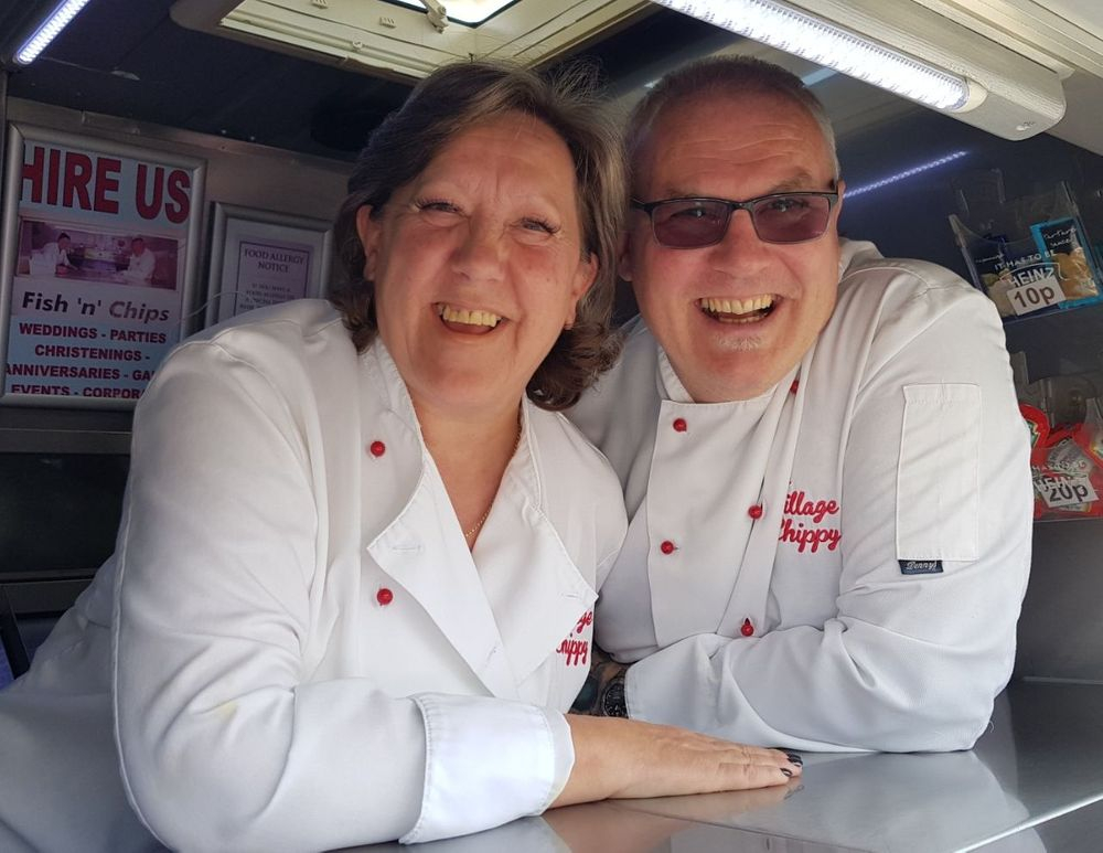 Owners Amanda and Garry inside the fish and chip catering van laughing their heads off after a very busy and long night. They look shattered.