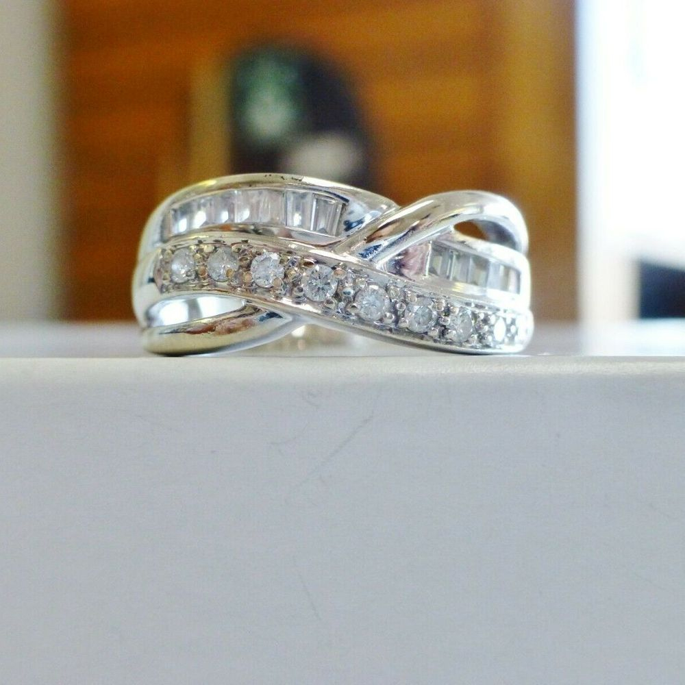 Round and baguette diamond crossover ring in white gold