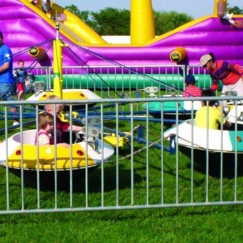 Kids riding a saucer ride at a fair