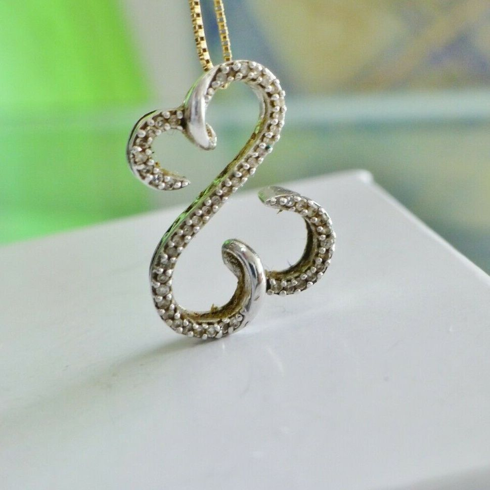 Diamond encrusted open hearts charm in white gold on a white gift box