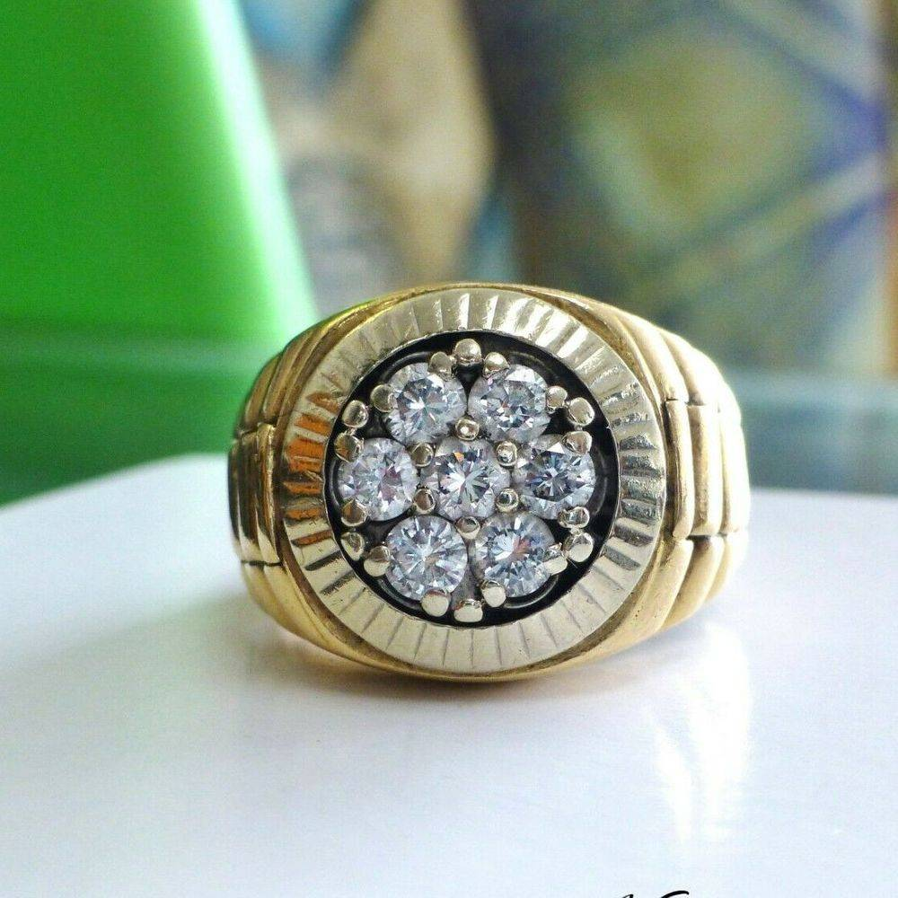 Seven round diamond cluster prong set on top of a yellow gold rolex style ring