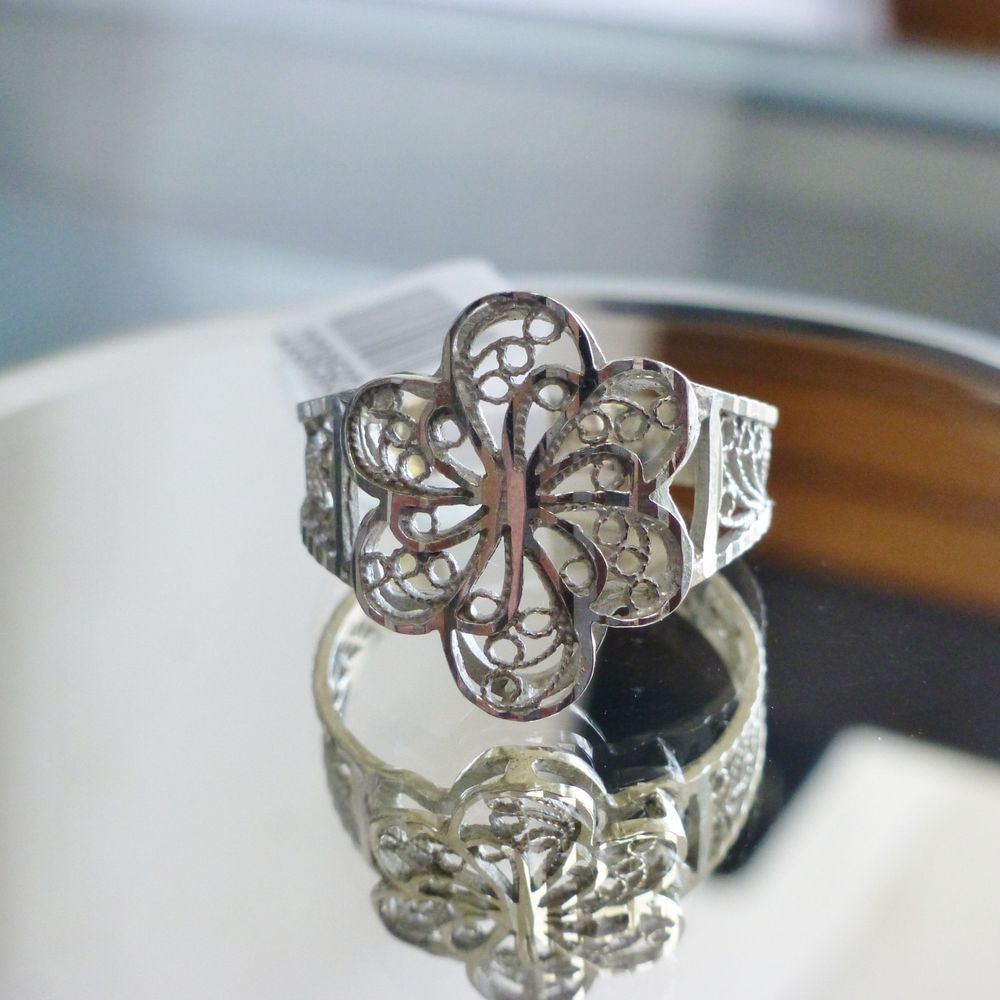 close up picture of a white gold diamond-cut swirling flower design ladies ring