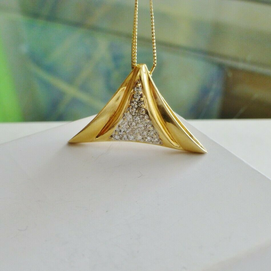 yellow gold framed triangular diamond cluster pendant hanging from a gold chain